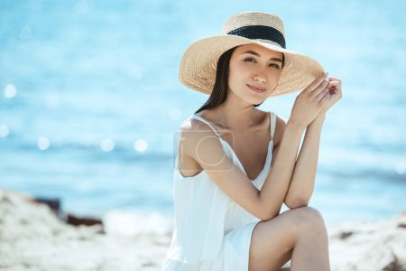 selective focus of attractive asian woman in straw hat on beach