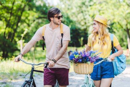 Photo pour Jeune couple avec sacs à dos et vélos dans le parc de sourire - image libre de droit