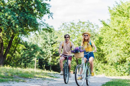 young couple riding retro bicycles in park on summer day