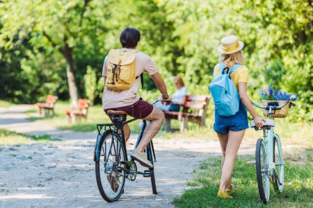 back view of couple with retro bicycle in park on summer day