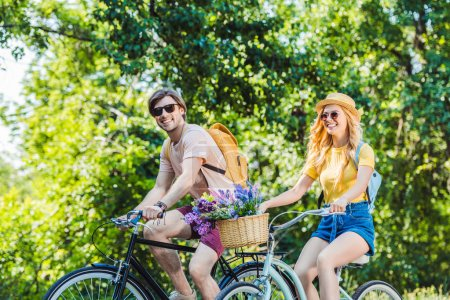 happy couple riding retro bicycles in park on summer day