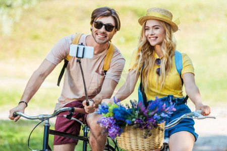 smiling couple in love with bicycles taking selfie in park on summer day