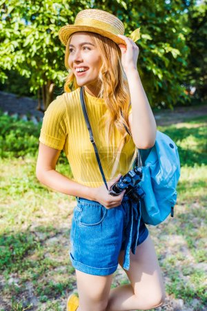 Photo for Young smiling woman in hat with photo camera walking in summer park - Royalty Free Image