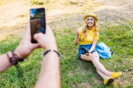 partial view of man taking picture of smiling girlfriend on green lawn in park