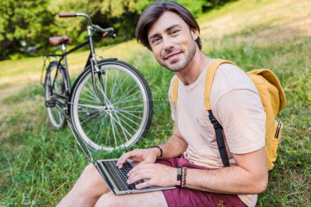 side view of smiling man with backpack, laptop and bicycle near by sitting on green grass in park