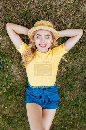 Photo pour Vue aérienne de la souriante jeune femme au chapeau reposant sur l'herbe verte dans le parc - image libre de droit