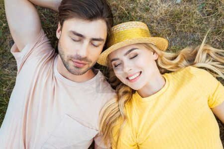 overhead view of couple in love resting on green grass in park
