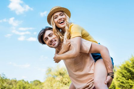 Photo for Low angle view of happy couple piggybacking in park - Royalty Free Image