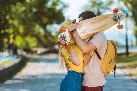 obscured view of couple kissing behind longboard in hands