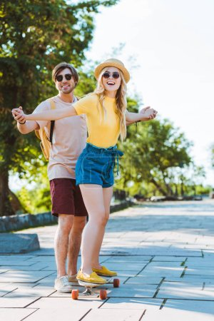 man helping girlfriend skating on longboard on street