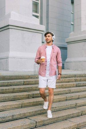 Photo pour Jeune homme au casque d'écoute avec ordinateur portable et le café pour aller sur la rue - image libre de droit