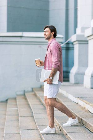 Photo pour Vue latérale du jeune homme avec ordinateur portable et café pour descendre les marches sur la rue - image libre de droit