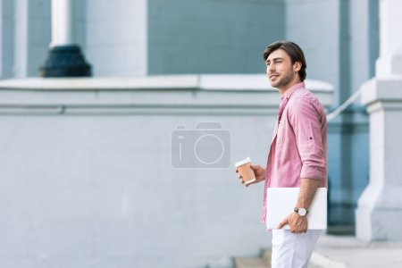 side view of young man with laptop and coffee to go on street