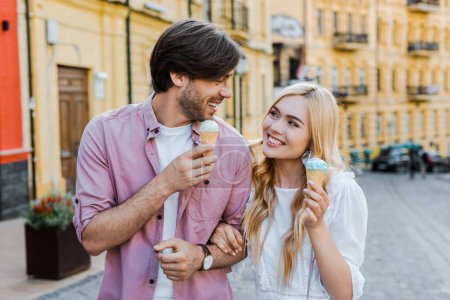 portrait of young couple with ice cream walking on street on summer day