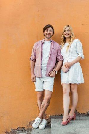 Photo pour Jeune couple élégant tenant la main tout en se tenant contre le mur de construction de la ville - image libre de droit