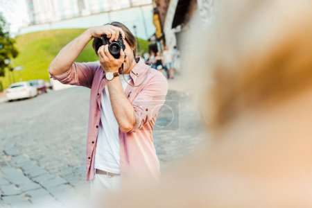 partial view of man taking picture of girlfriend on photo camera on street