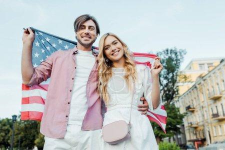 heureux jeune couple tenant le drapeau américain en mains, le concept de la fête de l'indépendance des Amériques
