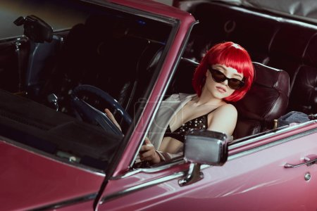 high angle view of beautiful girl in bra and sunglasses driving vintage car