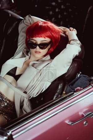 high angle view of stylish girl in trench coat and sunglasses sitting in retro car