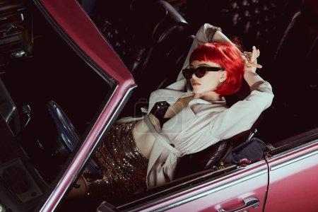 Photo pour Vue grand angle de fille élégante en trench coat et lunettes de soleil couché avec les mains derrière la tête dans la voiture rétro - image libre de droit