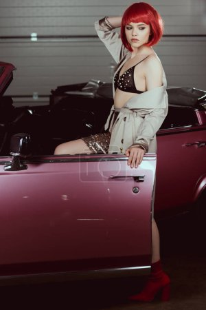 beautiful stylish girl opening vintage car and looking away