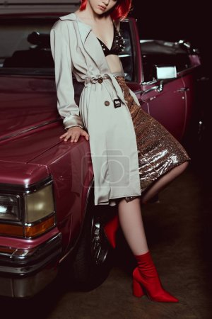 cropped shot of attractive girl in stylish trench coat leaning a vintage car