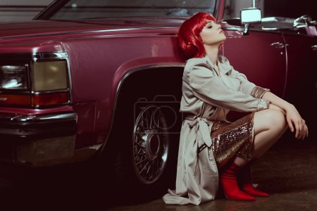 beautiful stylish young woman with closed eyes crouching near vintage car