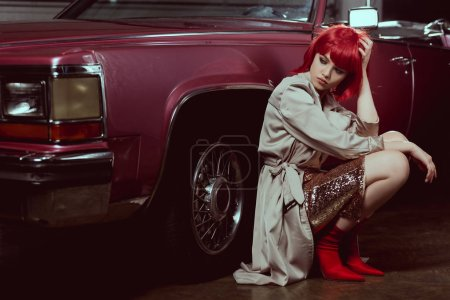 beautiful stylish young woman looking away while crouching near vintage car