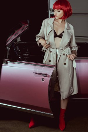 Photo pour Élégante jeune fille en soutien-gorge et trench-coat debout près de voiture rétro - image libre de droit