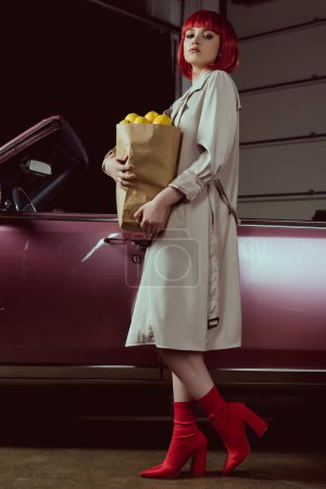 low angle view of young fashionable woman holding paper bag with lemons and looking at camera while standing near retro car