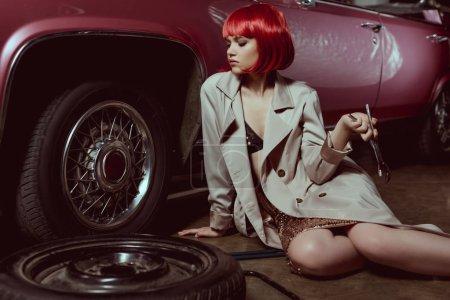 Photo pour Belle jeune femme en trench coat tenant clé et réparation de voiture - image libre de droit
