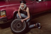 high angle view of beautiful stylish blonde girl in leather beret repairing car wheel and looking at camera