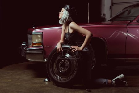 side view of sensual young woman repairing car wheel