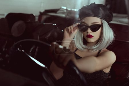 beautiful fashionable blonde girl in beret and sunglasses driving retro car