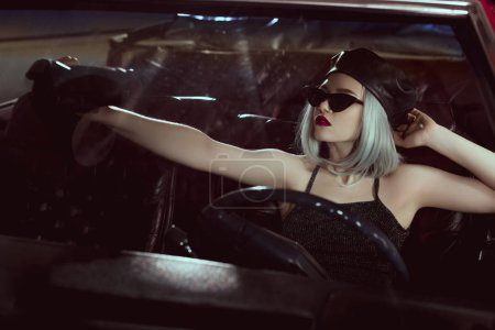 fashionable blonde girl in black beret and sunglasses sitting in retro car