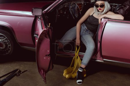 high angle view of stylish blonde girl in beret and sunglasses holding string bag with lemons while sitting in car