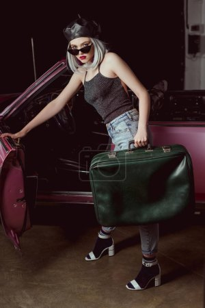 Photo for Stylish blonde woman in beret and sunglasses opening vintage car and holding old-fashioned suitcase - Royalty Free Image