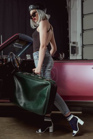 full length view of stylish blonde woman in sunglasses and beret holding old-fashioned suitcase bear retro car