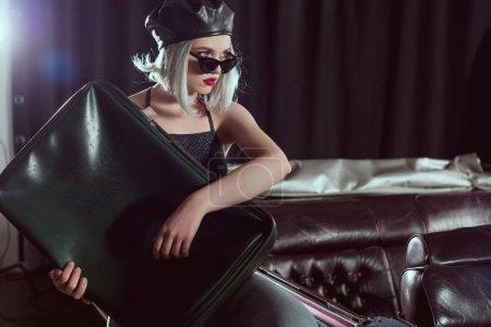 belle jeune femme à lunettes de soleil et béret tenant une valise vintage et à la recherche de suite en se tenant debout près de la voiture classique