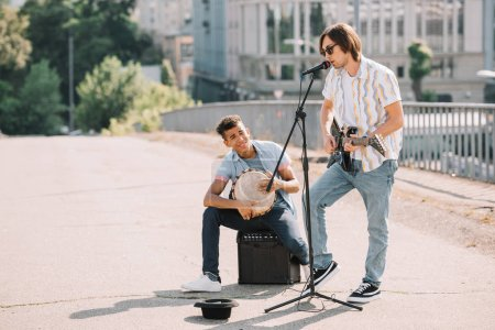 Photo for Young and happy male street musicians playing guitar and djembe in city - Royalty Free Image