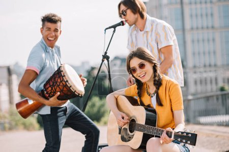 Multiracial young people performing om different musical instruments on street
