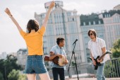 Team of young friends playing music and dancing in urban environment