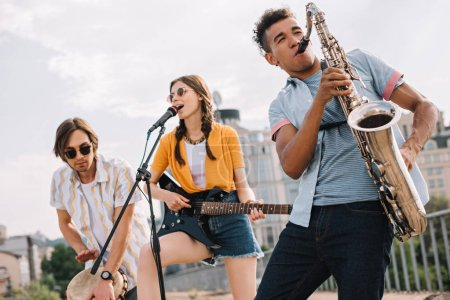 Photo for Multiracial young people with guitar, djembe and saxophone performing on street - Royalty Free Image
