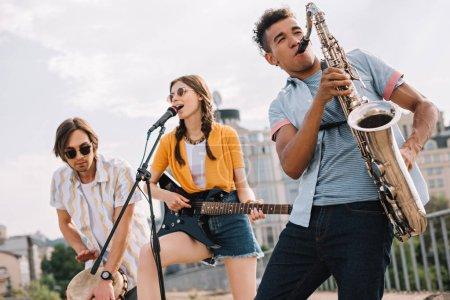 Photo pour Jeunes multiraciaux avec guitare, djembé et saxophone dans la rue - image libre de droit