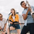 Multiracial young people with guitar, djembe and s...