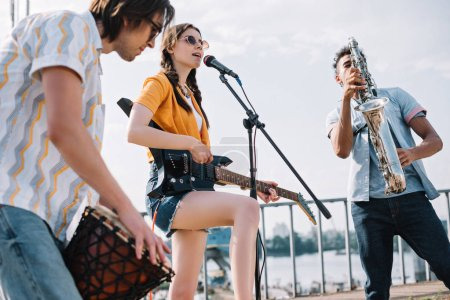 Multiracial young people with guitar, djembe and saxophone playing music on sunny city street