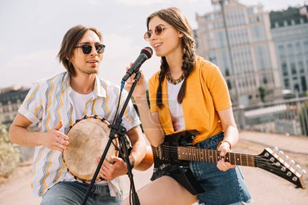 Male and female young people with guitar and djembe performing on street