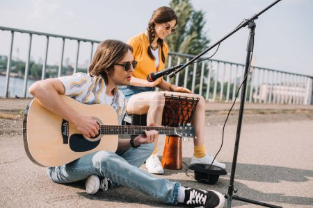 Young and happy couple street musicians playing in city