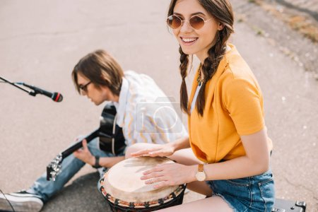 Photo for Couple of young street musicians smiling and performing in urban environment - Royalty Free Image