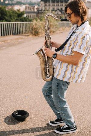 Young man with saxophone performing in urban environment